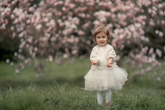 Porträt des glücklichen freudigen kindes in den weißen kleidern über baumblumenblütenhintergrund.