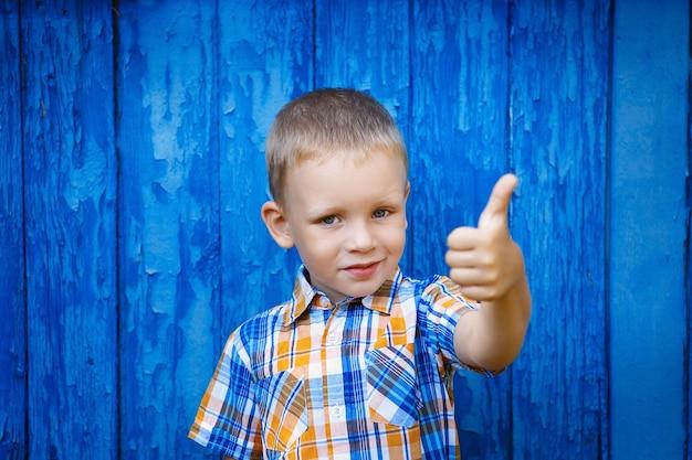 Porträt des glücklichen freudigen schönen kleinen jungen, der daumen gegen die blaue wand gestikuliert