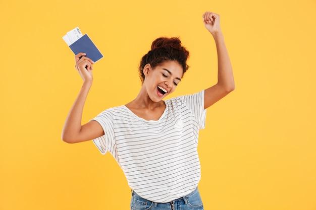 Porträt des glücklichen fröhlichen haltens des internationalen passes isoliert