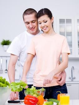Porträt des glücklichen fröhlichen jungen paares, das zusammen frühstück macht