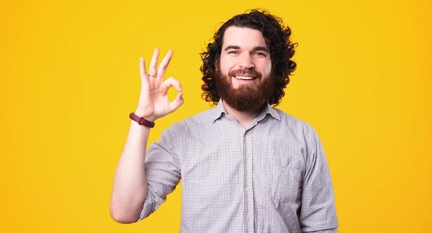 Porträt des glücklichen fröhlichen mannes mit dem lockigen haar, das ok geste zeigt