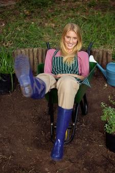 Porträt des glücklichen gärtners, der in der schubkarre am garten sitzt