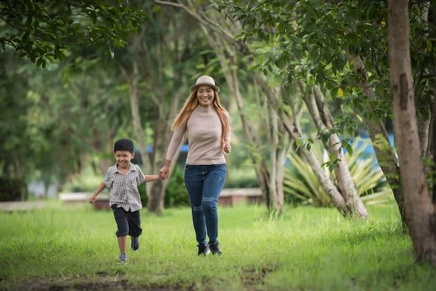 Porträt des glücklichen gehens der mutter und des sohns zusammen im park, der hand hält.