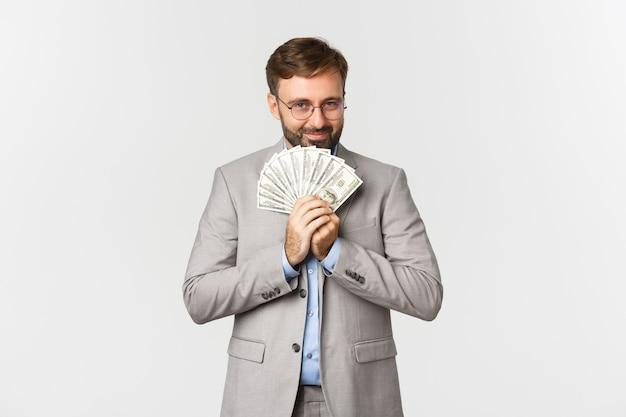 Porträt des glücklichen geschäftsmannes mit bart, tragen und brille, geld haltend