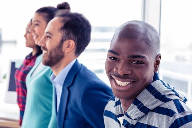 Porträt des glücklichen geschäftsmannes mit den kollegen, die im kreativen büro stehen