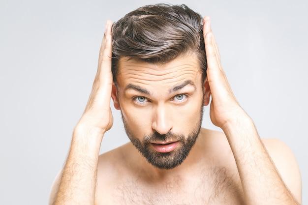 Porträt des glücklichen gesunden mannes, der sein haar mit den fingern kämmt