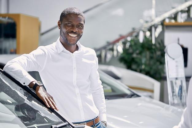 Porträt des glücklichen gutaussehenden afrikanischen mannes im autohaus
