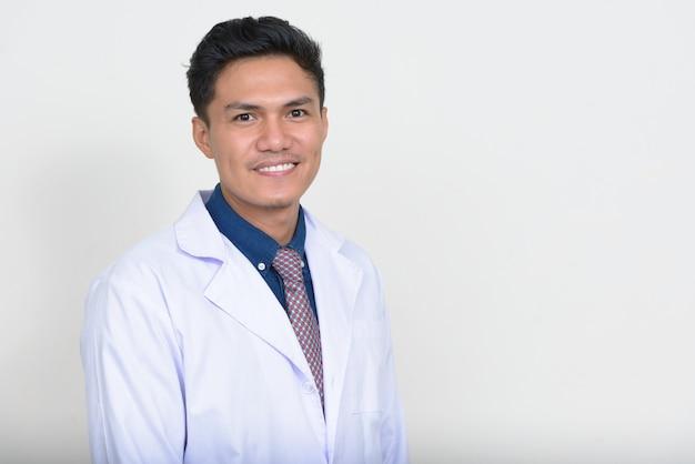 Porträt des glücklichen gutaussehenden asiatischen mannarztes lächelnd