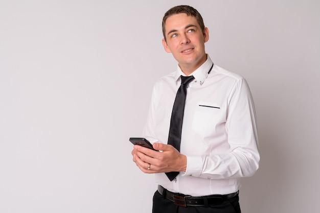 Porträt des glücklichen gutaussehenden geschäftsmannes, der telefon denkt und benutzt