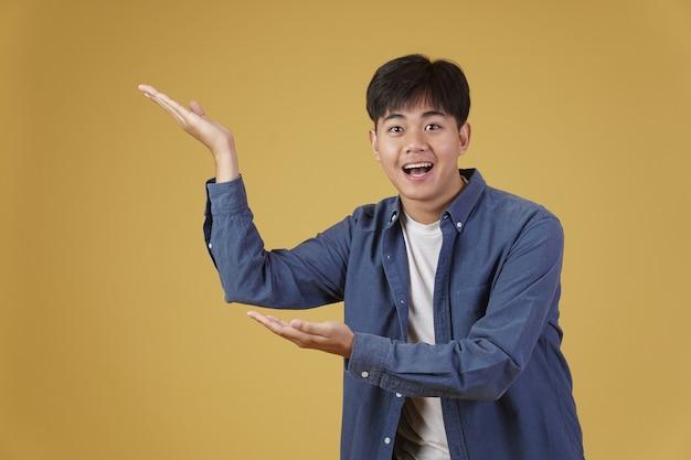 Porträt des glücklichen gutaussehenden jungen asiatischen mannes, der beiläufig gekleidet mit offener handflächengeste im copyspace präsentiert