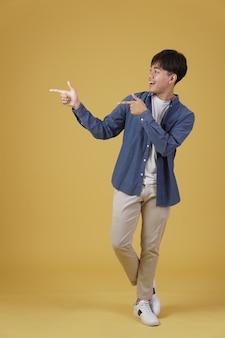 Porträt des glücklichen gutaussehenden jungen asiatischen mannes, der beiläufig gekleidete finger auf den isolierten copyspace gekleidet ist