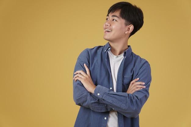 Porträt des glücklichen gutaussehenden jungen asiatischen mannes, der beiläufig mit verschränkter verschränkter armgeste isoliert gekleidet ist