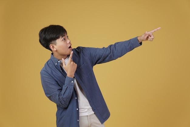 Porträt des glücklichen gutaussehenden jungen asiatischen mannes gekleidet, der beiläufig zeigt finger auf copyspace zeigt