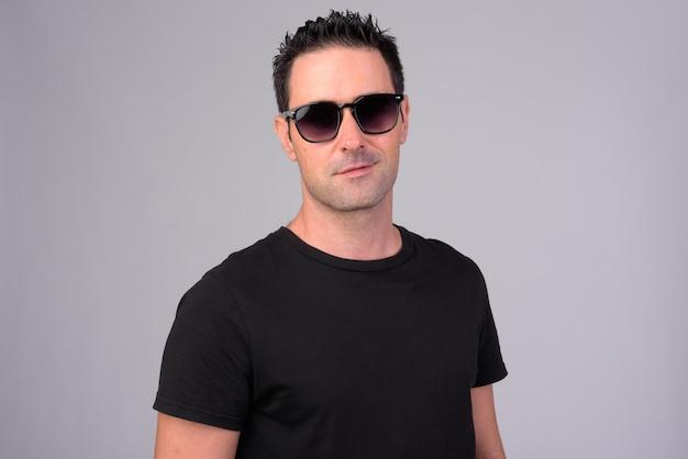 Porträt des glücklichen gutaussehenden mannes, der mit sonnenbrille auf weiß lächelt