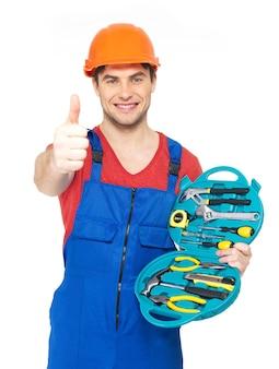 Porträt des glücklichen handwerkers mit werkzeugen, die daumen auf zeichen lokalisiert auf weiß zeigen