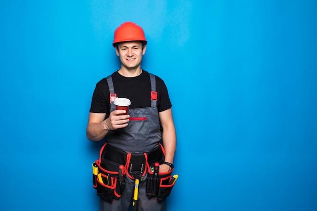 Porträt des glücklichen handwerkers mit werkzeuggürtel mit kaffee