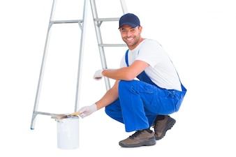 Porträt des glücklichen heimwerkers duckend durch farbendose