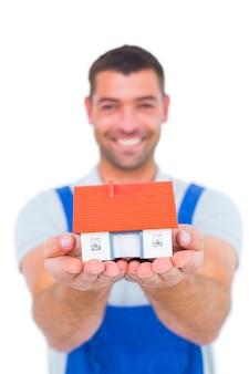 Porträt des glücklichen heimwerkers hausmodell halten