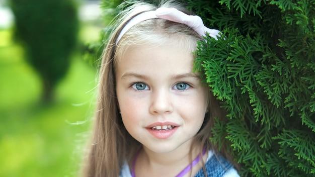 Porträt des glücklichen hübschen kindermädchens, das im sommerpark steht