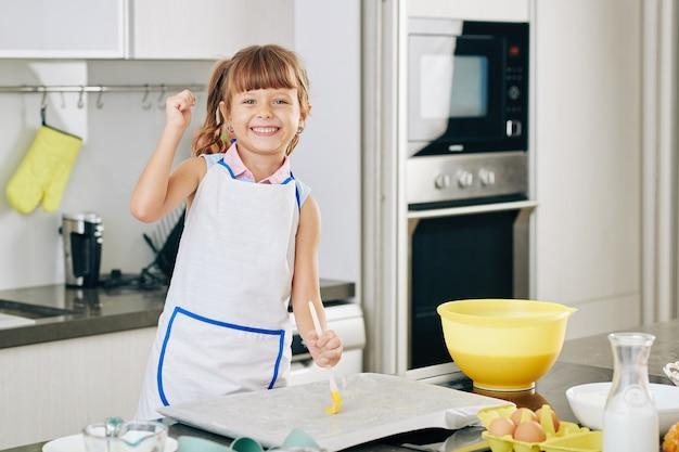Porträt des glücklichen jugendlichen mädchens, das backblech mit weicher butter bedeckt, bevor teig darauf gelegt wird