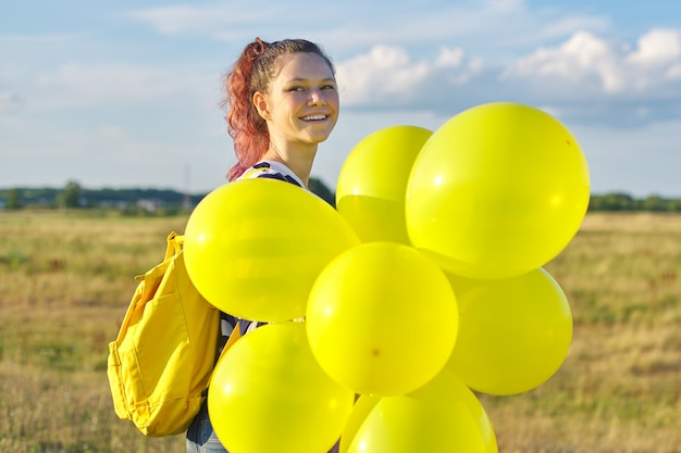 Porträt des glücklichen jugendlichmädchens 15 jahre alt mit gelben ballonen. himmel in den wolken, naturhintergrund. urlaub, natur, teenager, freudenkonzept