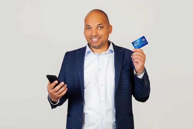 Porträt des glücklichen jungen afroamerikaner-geschäftsmannes, der kreditkarte verwendet, um online mit smartphone zu bezahlen.