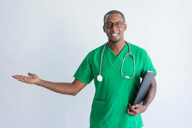 Porträt des glücklichen jungen afroamerikanerdoktors, der palme zeigt.