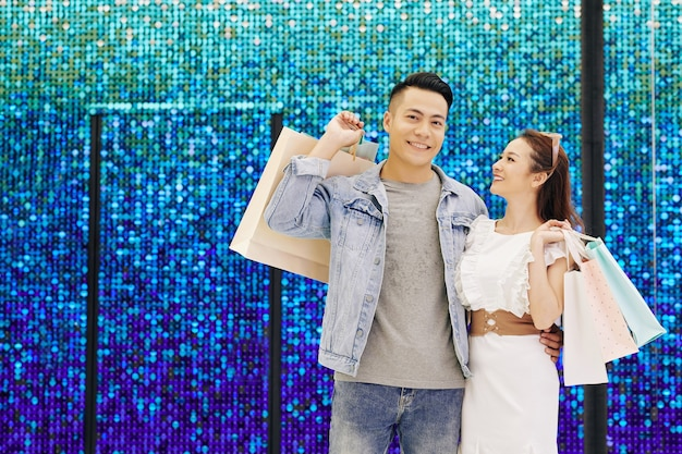 Porträt des glücklichen jungen asiatischen freundes und der freundin, die mit einkaufstüten gegen die funkelnde wand stehen