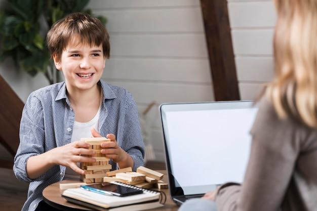 Porträt des glücklichen jungen, der jenga spielt