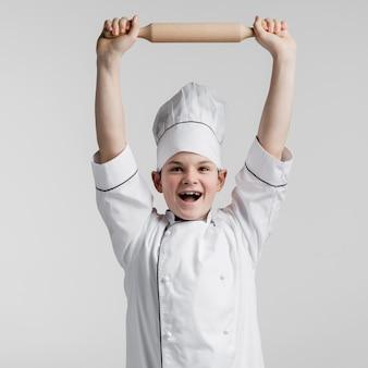 Porträt des glücklichen jungen, der nudelholz hält