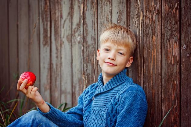 Porträt des glücklichen jungen einen apfel draußen im garten essend