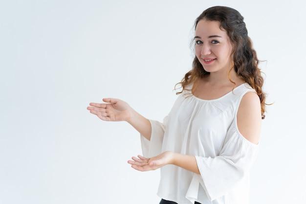 Porträt des glücklichen jungen kaukasischen frauenwerbungsproduktes