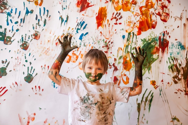 Porträt des glücklichen jungen kindes, das mit aquarell spielt. kindergesicht und kleidung unordentlich mit farben bemalt. konzept kinderspaß, kunstspiele und rowdytum. farbbild für holi-festival. platz kopieren