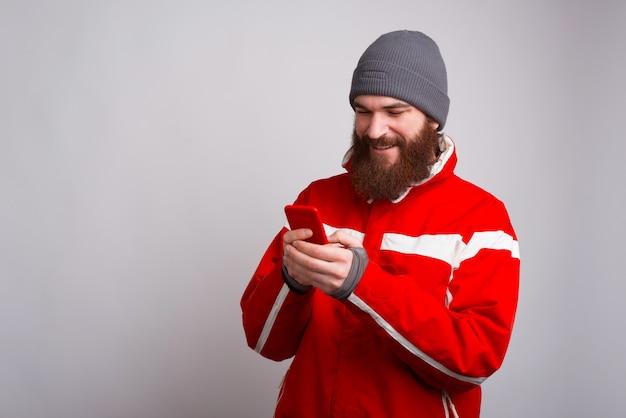 Porträt des glücklichen jungen kletterers in der winterkleidung unter verwendung des smartphones