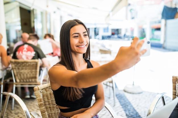 Porträt des glücklichen jungen lateinamerikanischen mädchens, das selfie mit handy nimmt, während an einem café draußen sitzt