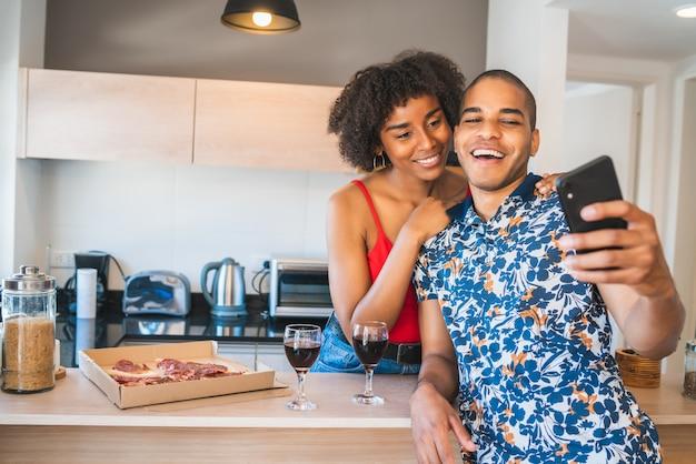 Porträt des glücklichen jungen lateinamerikanischen paares, das ein selfie mit dem handy beim abendessen im neuen zuhause nimmt. lebensstil- und beziehungskonzept.