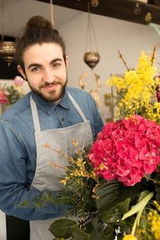 Porträt des glücklichen jungen männlichen floristen mit blumenblumenstrauß