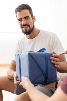 Porträt des glücklichen jungen mannes, der blau nimmt, wickelte geschenkbox vom freund ein