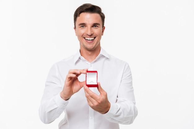 Porträt des glücklichen jungen mannes, der offene schachtel zeigt