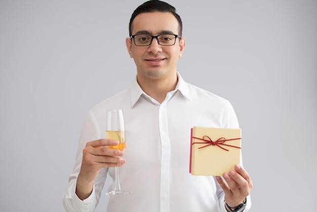 Porträt des glücklichen jungen mannes, der sektkelch und geschenkbox hält