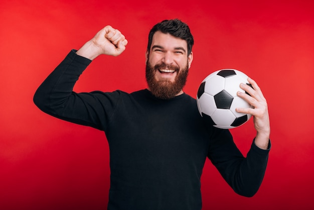 Porträt des glücklichen jungen mannes, der sieg feiert und fußball hält