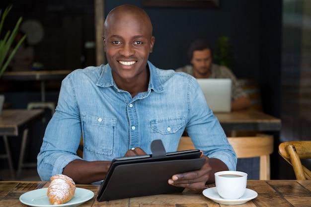 Porträt des glücklichen jungen mannes, der tablet-computer am tisch im kaffeehaus verwendet