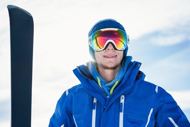 Porträt des glücklichen jungen mannes lokalisiert mit snowboard