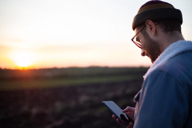 Porträt des glücklichen jungen mannes mit smartphone in der hand auf hintergrund des sonnenuntergangs