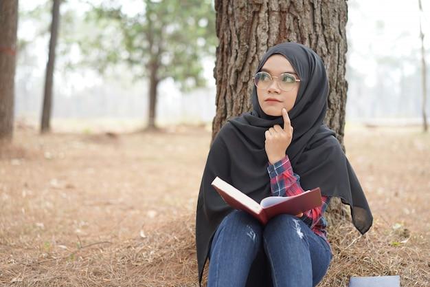 Porträt des glücklichen jungen moslemischen frauenschwarzen hijab und des schottischen hemdes, die ein buch im herbstsaisonhintergrund lesen.