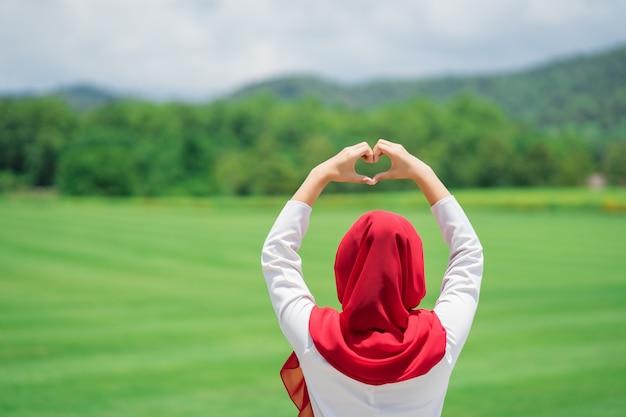 Porträt des glücklichen jungen moslemischen roten hijab am grünen feld