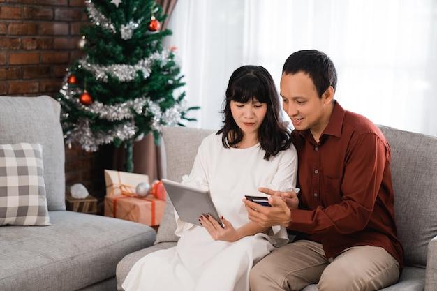 Porträt des glücklichen jungen paares, das sachen online mit kreditkarte am weihnachtstag kauft