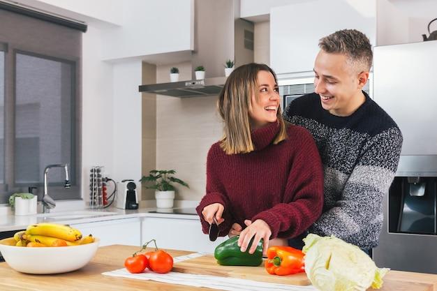 Porträt des glücklichen jungen paares, das veganes essen zusammen in einer modernen küche kocht