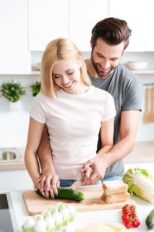 Porträt des glücklichen jungen paares, das zusammen in der küche kocht