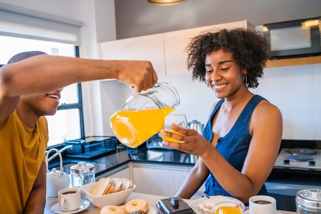 Porträt des glücklichen jungen paares, das zusammen zu hause frühstückt. beziehungs- und lebensstilkonzept.